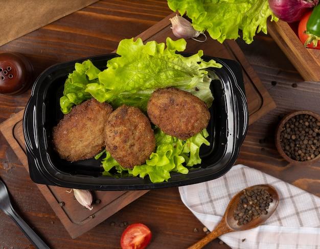 Вынос котлеты из говядины с салатом в черном контейнере.