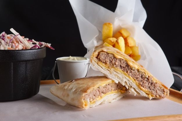 Beef cutlet with cheese rolled in pita wuth fried potato and red cabbage