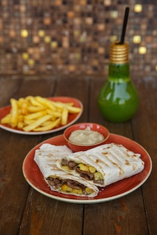 Beef doner wrap in flatbread served with fries and mayonnaise