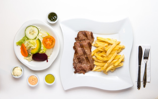 Beef and french fries with salad and creams