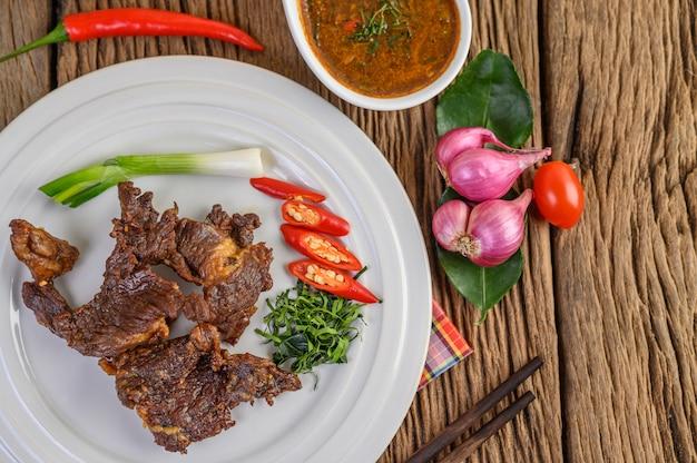 Говядина жареная тайская еда на белой тарелке с зеленым луком, листьями лайма кафрского, чили, красным луком и помидорами.