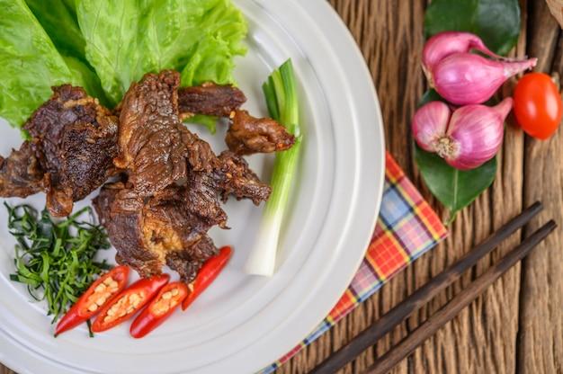 Говядина жареная тайская еда на белой тарелке с зеленым луком, листьями лайма каффир, чили, салат, красный лук и помидоры.
