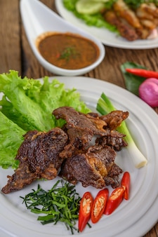 Beef fried thai food on a white plate with spring onion, kaffir lime leaves, chilies, salad and chili paste in a cup.