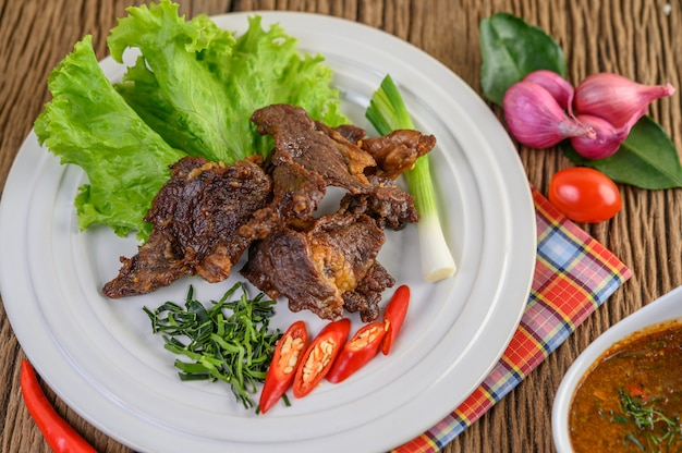 Beef fried thai food on a white plate with spring onion, kaffir lime leaves, chilies, salad, red onions and tomatoes.