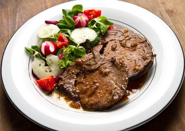 Говядина, украшенная свежим салатом, помидорами, редисом и огурцами