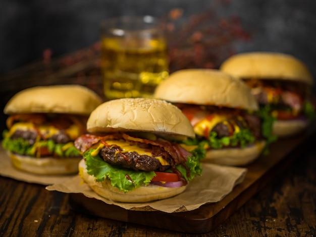 ロフトの背景にビールを添えた木の板で提供されるビーフハンバーガー。