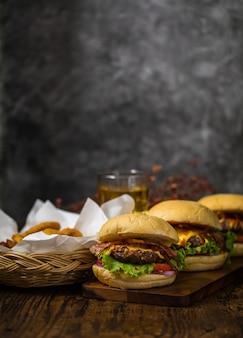 揚げタマネギ、ほうれん草、ケチャップ、コショウ、チーズを添えたビーフハンバーガーを木の板に盛り付け、ロフトの背景にコピースペースのあるビールを添えます。
