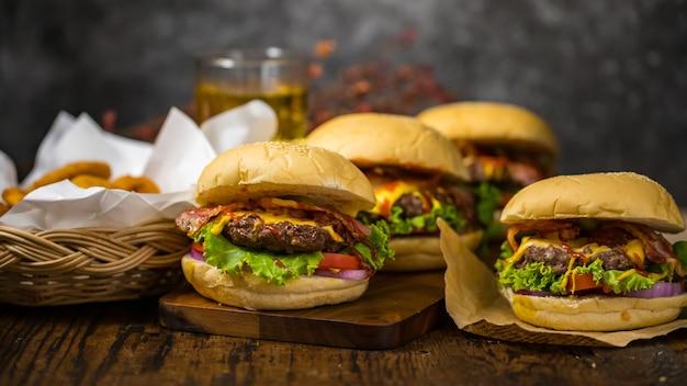 揚げタマネギ、ほうれん草、ケチャップ、コショウ、チーズを添えたビーフハンバーガーを、ロフトの背景にビールを添えた木の板に盛り付けました。