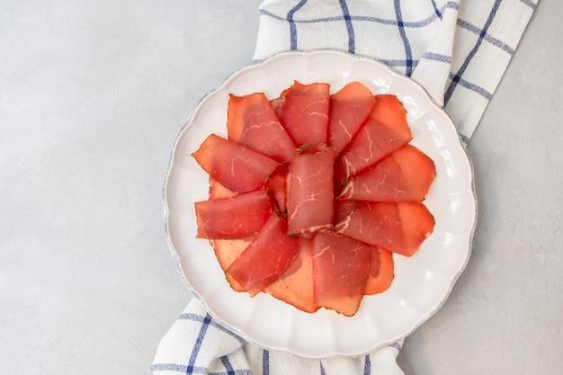 Вяленые куски говядины вяленое мясо говядины на белой тарелке, вид сверху, плоская кладка с копией пространства