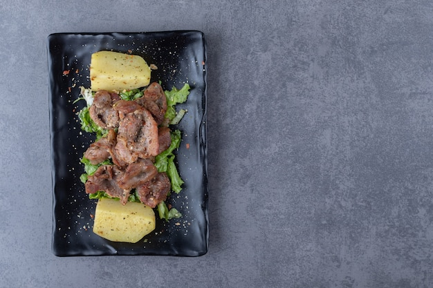 검은 접시에 쇠고기 케밥과 삶은 감자.