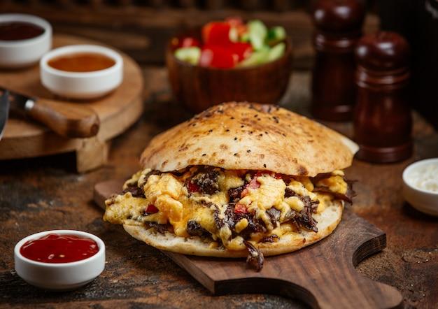 Донер из говяжьего кебаба в лаваше с плавленым сыром на деревянной доске