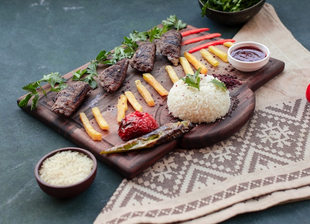 Beef kebab, fried potato sticks, grilled foods, rice garnish and sauce on a wooden board.