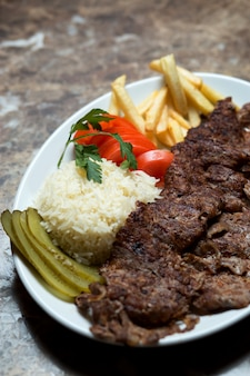 Beef kebab plate with french fries, cucumber pickles, rice and tomato