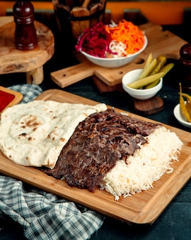 Beef kebab served with rice and flatbread placed on wood serving board