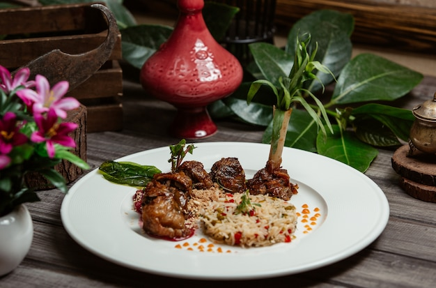 Beef kebab with rice garnish and pomegranate seeds