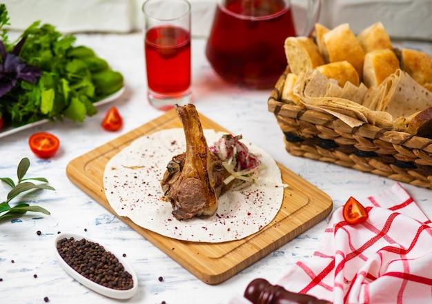 Отбивная из говяжьего ягненка в лаваше на деревянной тарелке с луковым салатом, хлебом, овощами и вином