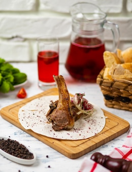 Beef lamb chop meal in lavash on wooden plate with bread, vegetabels and wine