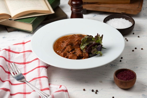 Beef lamb meat sauteed, stew in browh and tomato sauce, served with vegetables and sumakh.