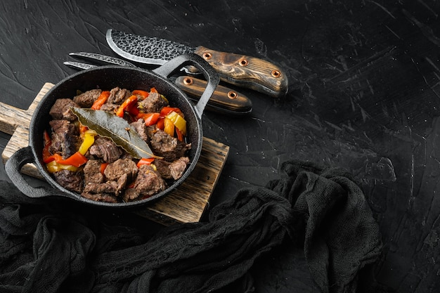 검은 돌 테이블에 주철 프라이팬에 쇠고기 고기와 야채 스튜 제공