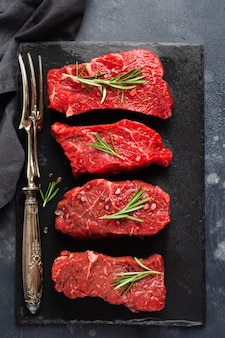 Beef meat. four fresh raw beef steak with spices, onions and rosemary on dark slate or concrete wall. top view.