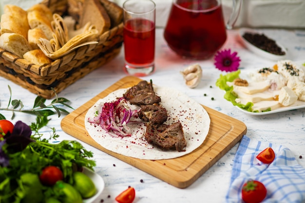 Beef meat kebab with onions, sumakh and lavash on a wooden plate served with wine and vegetables