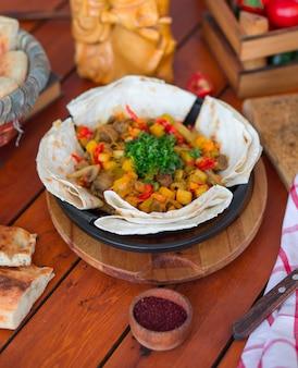 Говядина тушеная с картофелем и нарезанными овощами, подается с лавашем.