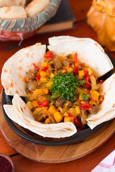 Beef meat stew with potatoes and chopped vegetables served with lavash .