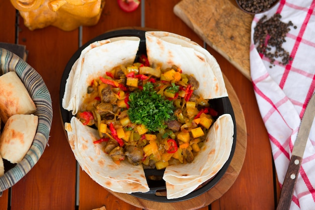 Beef meat stew with potatoes and chopped vegetables served with lavash