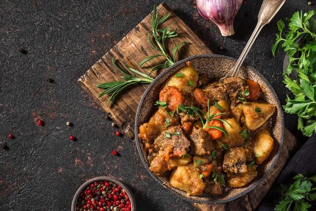黒い表面にスプーンで皿にジャガイモ、ハーブ、ニンジンを煮込んだ牛肉