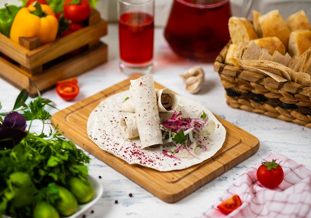 Beef meat traditional turkish kebap durum lavash served on a wooden board with vegetables wine and bread