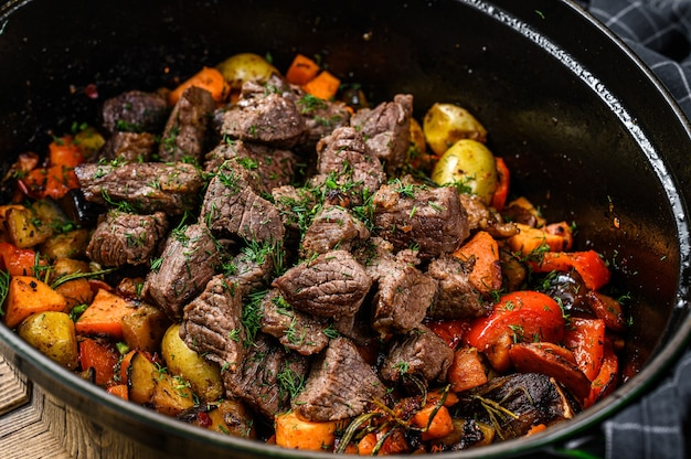 Beef meat and vegetables stew in black baking dish