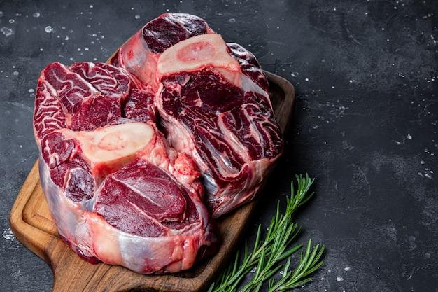 어두운 회색 배경에 로즈마리와 함께 커팅 보드에 쇠고기 고기 마녀 뼈를 닫습니다. 고품질 사진