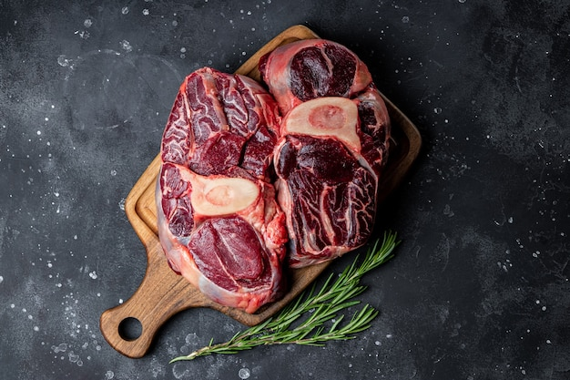 어두운 회색 배경 평면도에 로즈마리와 함께 커팅 보드에 쇠고기 고기 마녀 뼈. 고품질 사진