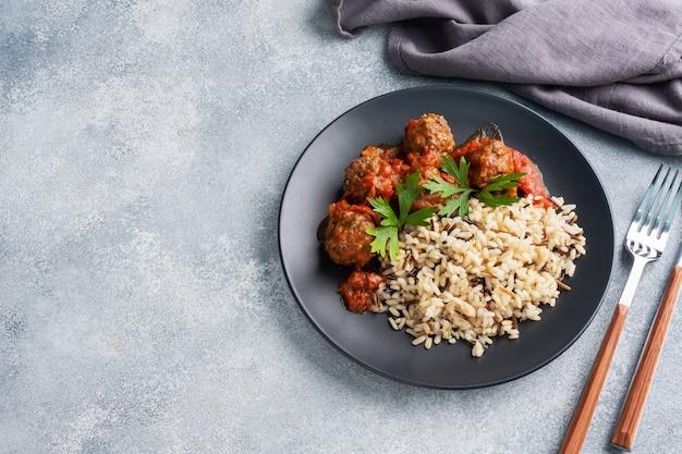 Фрикадельки из говядины и коричневый рис на тарелку.