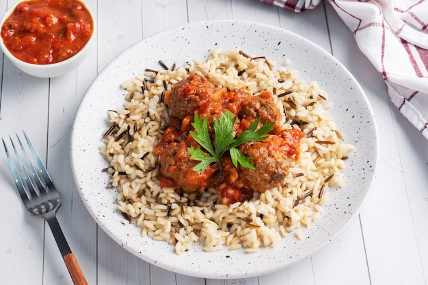 Beef meatballs and brown rice on a plate.