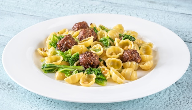 Beef meatballs with pasta, kale and pine nuts