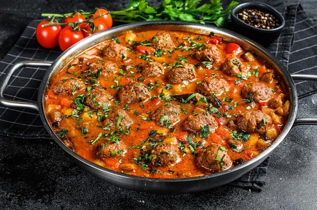 Котлеты из говядины с томатным соусом и овощами на сковороде