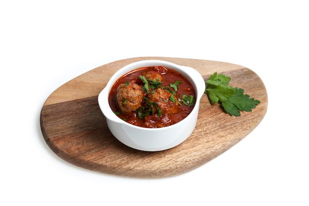 나무 서빙 보드에 흰색 그릇에 토마토 소스와 쇠고기 미트볼.