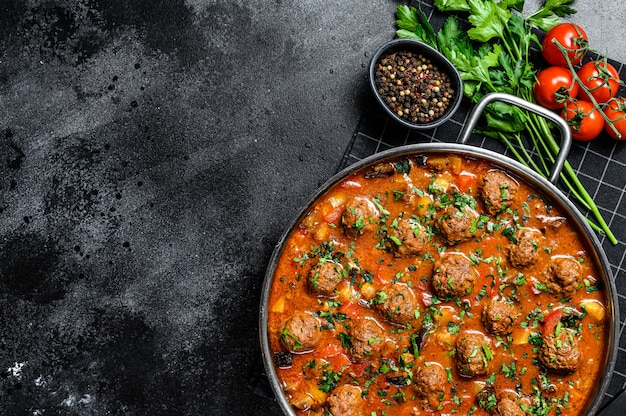 Beef meatballs with tomato sauce and vegetables in a pan. black background. top view. space for text
