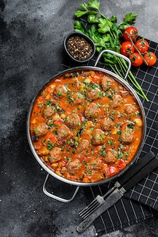 Beef meatballs with tomato sauce and vegetables in a pan. black background. top view