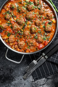 Beef meatballs with tomato sauce and vegetables in a pan. top view.