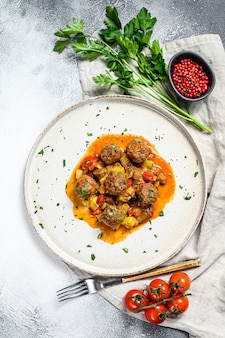 Beef meatballs with tomato sauce and vegetables in a pan. top view