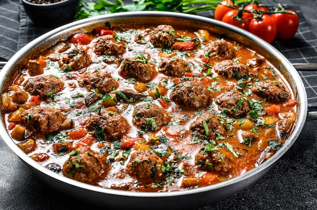Beef meatballs with tomato sauce and vegetables in a pan