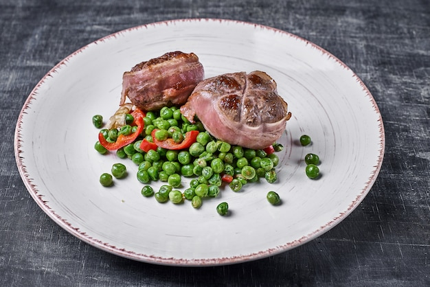 Beef medallions wrapped in bacon, serve with green peas and on a plate on wooden background.