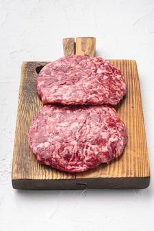 흰 돌 배경에 쇠고기 다진 고기 커틀릿 세트