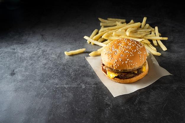 牛肉または豚肉。ハンバーガーとフライドポテト、暗い背景に