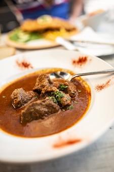 牛肉または子牛のグーラッシュをジュースシチューと一緒に皿に盛り付け、皿に盛り付けます。