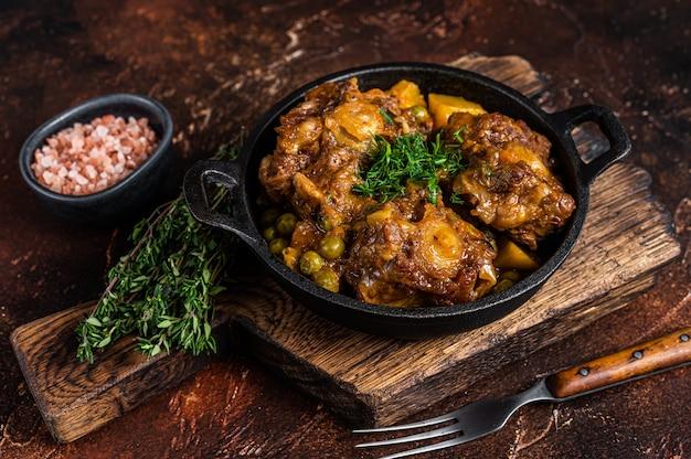 Тушеные бычьи хвосты с вином и овощами на сковороде
