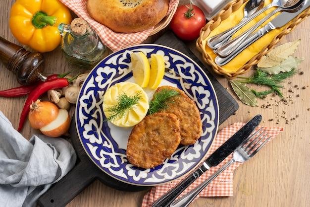伝統的なウズベキスタンのプレートにマッシュポテト、レモン、ディルを添えたビーフパテ
