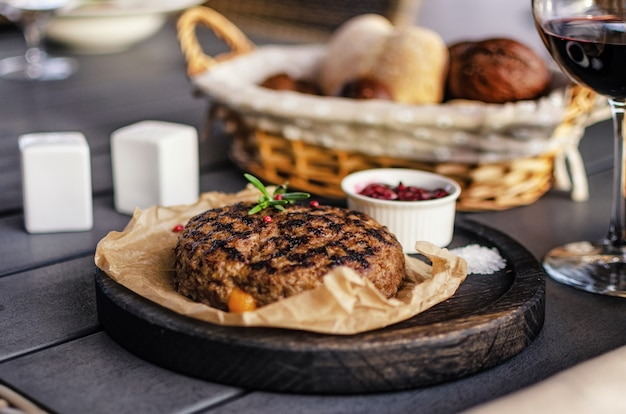 Beef patty served in a wooden plate on a wooden table